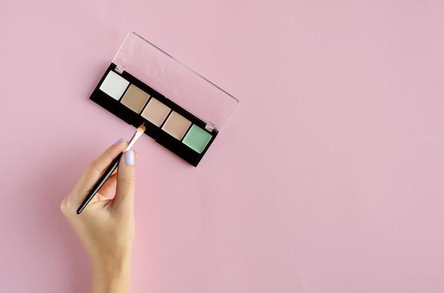 化粧影パレット構成を持つ手