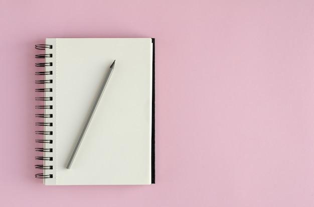 ピンクの背景に鉛筆の組成とメモ帳。