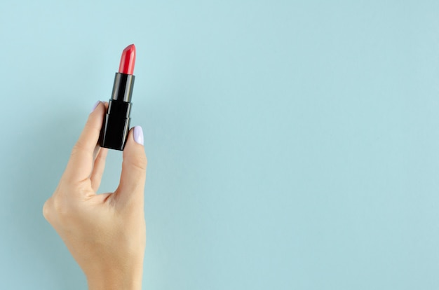 青色の背景に赤い口紅の組成を持つ手。