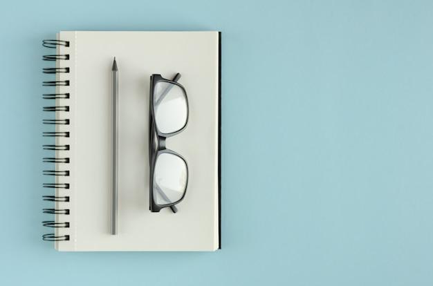 青色の背景に眼鏡と鉛筆の組成とメモ帳。