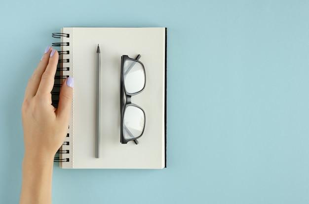 青の背景にメモ帳、眼鏡、鉛筆の組成を持つ手。
