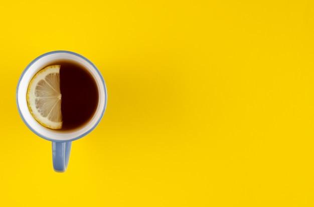 黄色の背景にレモンスライス構成と青茶カップ。