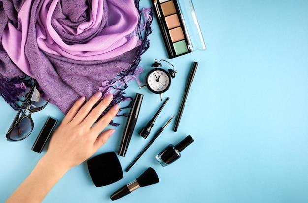 Состав различных косметических продуктов с рукой на синем фоне
