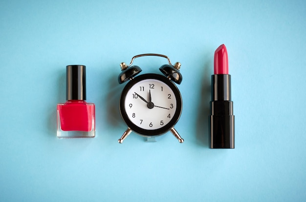 Черная композиция будильник с косметикой на синем фоне