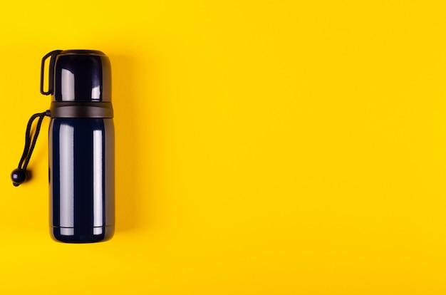 黄色の背景に暗い魔法瓶組成。平置き