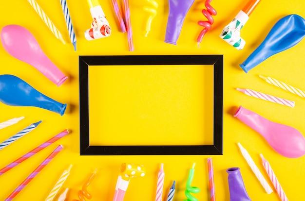 Покрашенный состав свечей и воздушных шаров на желтом украшении предпосылки, партии и торжества.
