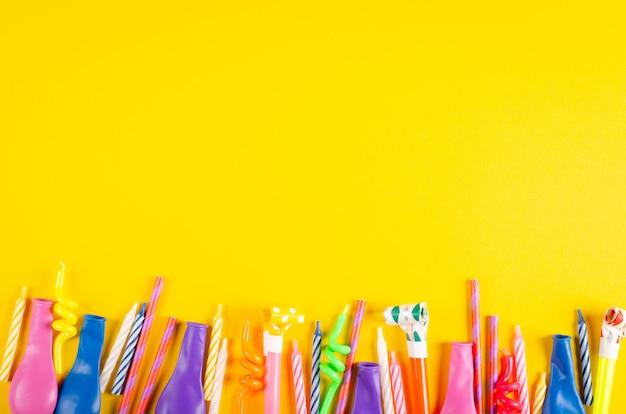 黄色の背景、パーティー、お祝いの装飾の色のキャンドルと気球の組成。