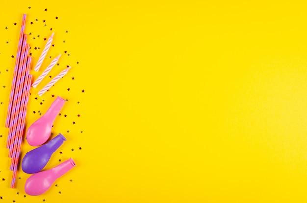 黄色の背景、パーティー、お祝いの装飾の色のストローと気球の組成。