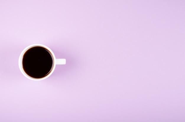 Состав кофейной чашки на фиолетовой предпосылке. квартира лежала.