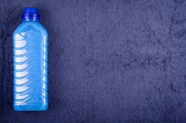 Синий кондиционер в бутылке на текстильной композиции.