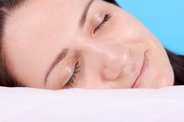 Брюнетка девушка спать на белой подушке, закрытые глаза. изолированные на синем фоне.