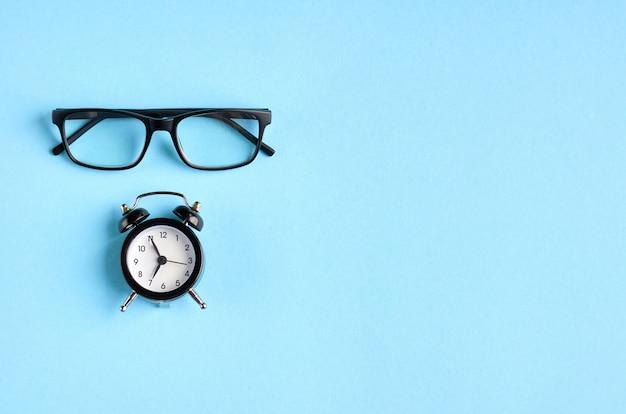 黒い眼鏡と青い表面上の目覚まし時計。