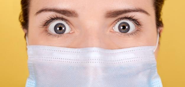 Портрет брюнетка девушка с страшные глаза в медицинской маске, широко открытые глаза с ужасом.