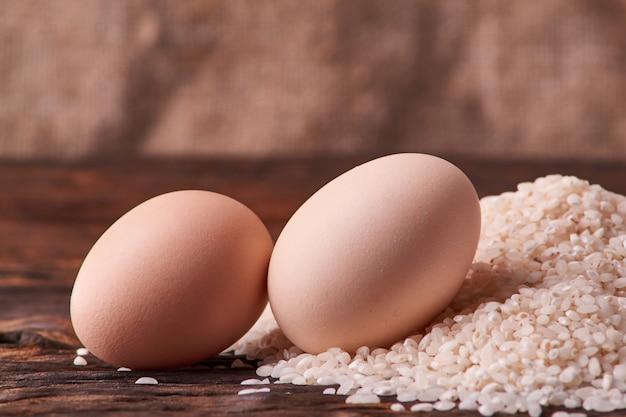 Куча риса и сырые яйца на деревянный стол