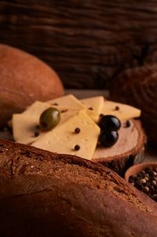 異なるパンの間の木製の机の上のチーズのスライス