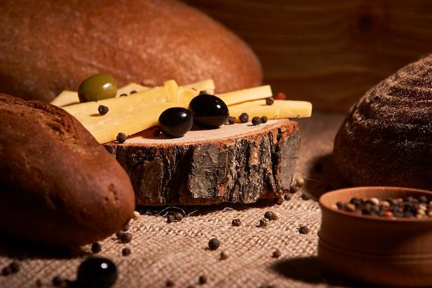 異なるパンの間の木製の机の上のチーズのスライス。テキストのための場所