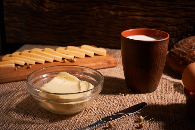 Масло и сыры и молоко на завтрак, на деревенский деревянный фон с копией пространства. утренний завтрак