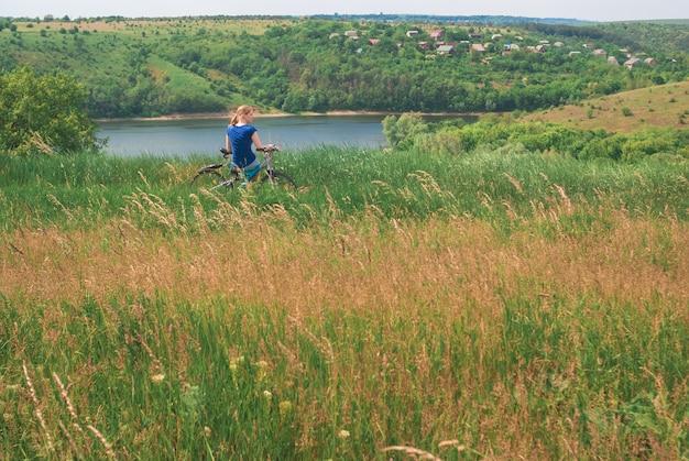 川の岸に自転車を持つ少女。女の子が自転車のテントの近くで自転車に座っています。旅行と自由のトン。