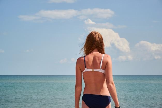 水着と海の背景に分離された黒いサングラスの若い女性。美少女