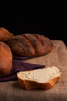 Пекарня золото деревенском хрустящие буханки хлеба и булочки на фоне черной доске. натюрморт, запечатленный сверху