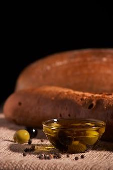 オリーブオイル、オリーブと焼きたてのパンのバゲット。チーズと木製の背景にローズマリー。おいしい朝食