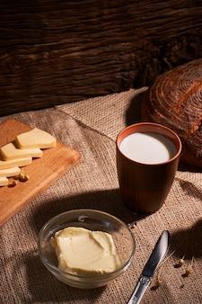 コピースペースを持つ素朴な木製の背景の上のバターとヨーグルト、朝食のミルク。朝の朝食