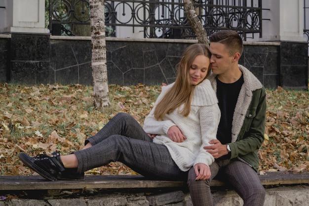 愛のカップルは、美しい秋の日を楽しんで、公園の秋の落ち葉の上に立ちます。男は女の子を抱擁