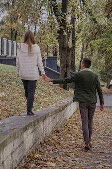 秋の公園で幸せなカップルは楽しい時間を過ごします。色の秋