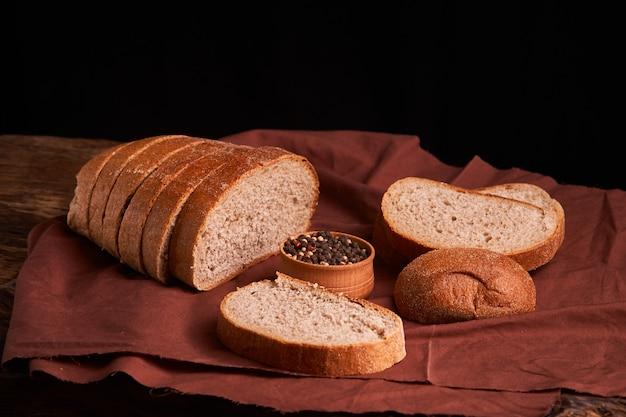 ベーカリー。黒い黒板背景にパンとパンの金の素朴な無愛想なパン。上から撮影した静物
