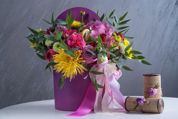 アジサイ、バラ、サンティーニ、イースターとライラックの花のブーケ。白いテーブルの上。