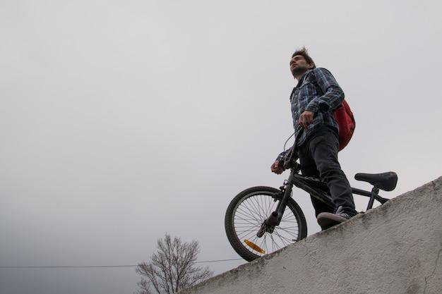 Он велосипедист на велосипеде на фоне неба, темнеет