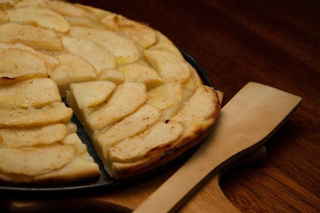 Домашний яблочный пирог и кусок пирога с кусочками яблока на доске кука.