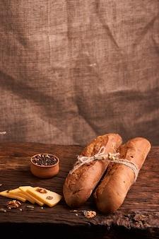 Две свежие багеты на темном деревянном столе