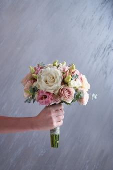 Букет свадьбы владением руки женщины на серой предпосылке. закрыть