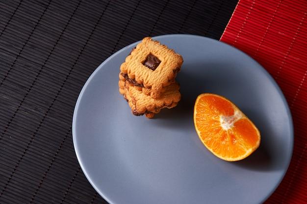 Шоколадное печенье и апельсин на серой тарелке и по красному с черным столом