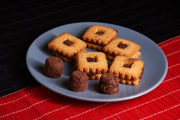 Шоколадное печенье с песком, сложенное на тарелке, готовое к подаче на синюю тарелку