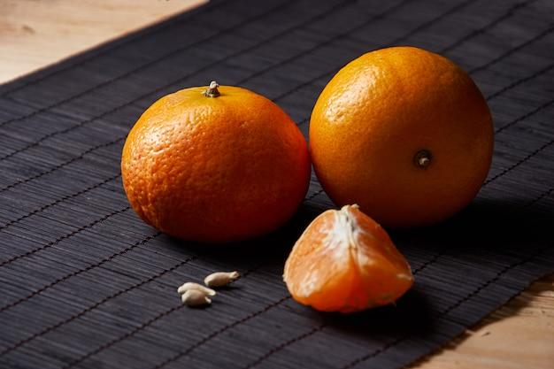 Сочные оранжевые мандарины на черном с красным стилем стола