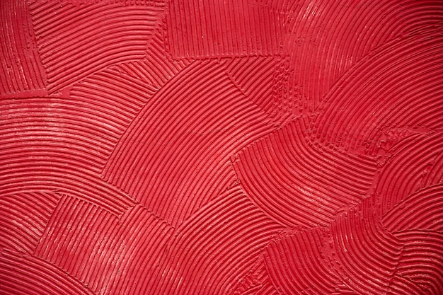 Стены текстуры с глубокими круговыми мазками замазки, покрытые красной краской.