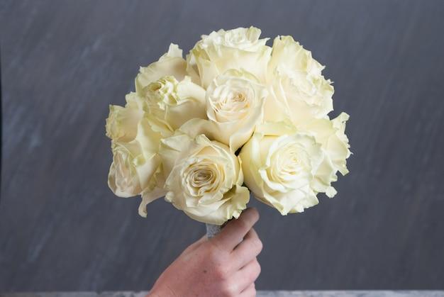 Свадебный букет с белыми розами на сером фоне. закрыть