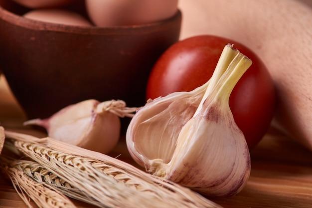 Чеснок на деревянном столе с яйцами в глиняной миске, помидор, баттлдор