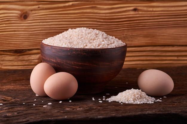 Белый рис в глиняной миске на столе и яйца на фоне дерева