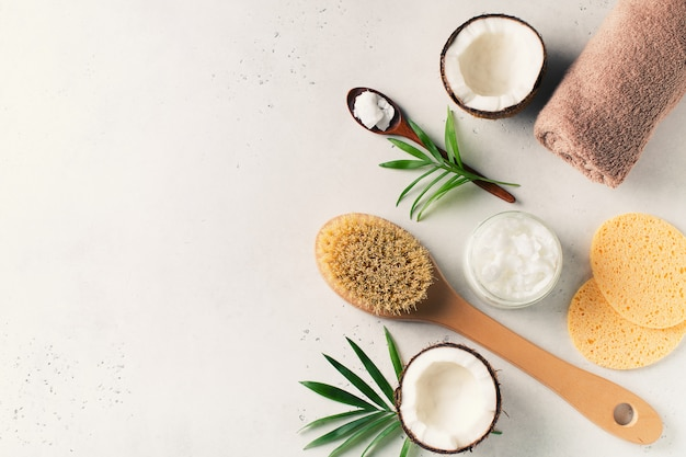 Щетка сухого массажа с кокосовым маслом, концепция здоровья и здоровья с аксессуарами на белом фоне