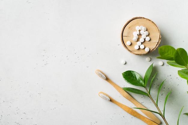 木製の生態学的な歯ブラシと白い背景の上の歯磨き粉のタブレット