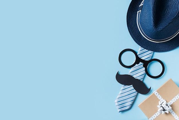 Концепция отцов день с шляпу, очки и галстук на синем фоне