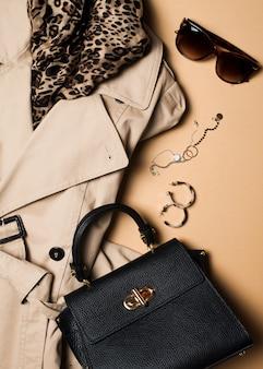 女性のファッションの服やアクセサリーフラットレイ、バッグ、メガネ、デニムとウエスタンブーツとベージュのトレンチコート