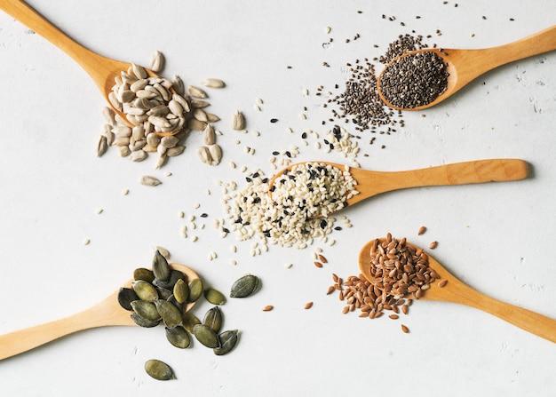Смешивание семян в конце ложки вверх на белой предпосылке. веганские и вегетарианские блюда