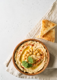 ひよこ豆、ピタとパセリの白い背景の上の木の板でフムスディップ