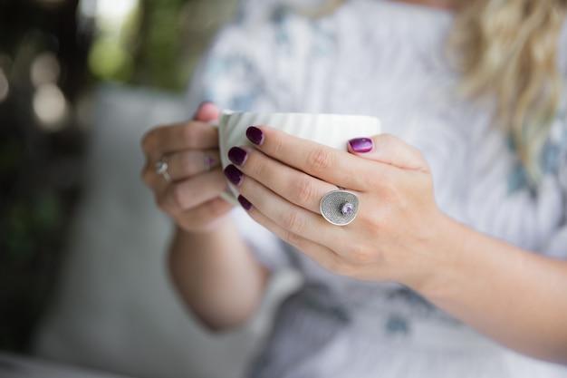 Женская рука с кольцом держит чашку капучино