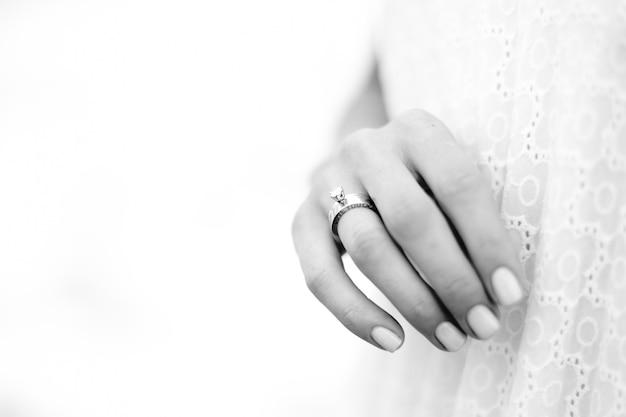 海の背景を持つ結婚指輪を持つ美しい女性手。