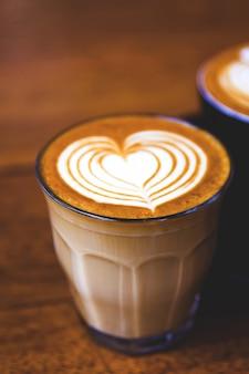 木製のテーブルの上の熱いラテコーヒーのカップ